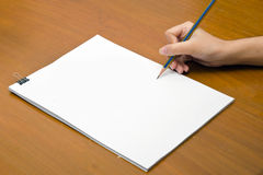 Hand holding pencil and white paper close-up view Stock Image
