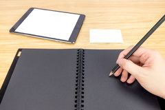Hand holding pencil writing on blank black book with table and b Royalty Free Stock Photos