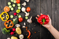 Hand holding pepper and fresh vegetables on wooden table background Royalty Free Stock Images