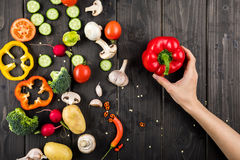 Hand holding pepper and fresh vegetables on wooden table background Stock Images