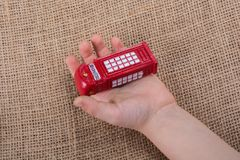 Hand holding a red phone booth. Hand holding a phone booth on a brown background Stock Photo