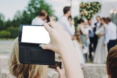 Hand holding phone with empty screen and taking photo of gorgeous bride and stylish groom with guests at wedding reception in. Restaurant. Photo booth royalty free stock images