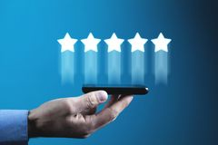 Hand holding phone with five stars. Increase rating stock photography