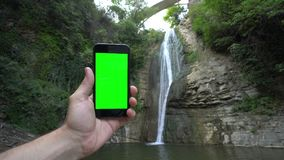 A Hand Holding a Phone with a Green Screen. A hand holding using a smapthone with a green screen oute. Taking pictures of the waterfall. Close-up shot Stock Images