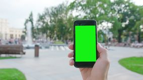 A Hand Holding a Phone with a Green Screen