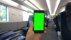 Hand Holding a Phone with a Green Screen on the Train. Tbilisi, Georgia - 15 September 2017: A hand holding using a smapthone with a green screen on the train Stock Images