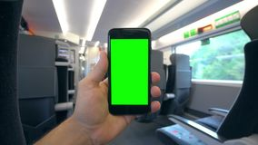 Hand Holding a Phone with a Green Screen on the Train. Tbilisi, Georgia - 15 September 2017: A hand holding using a smapthone with a green screen on the train Royalty Free Stock Image