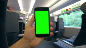 Hand Holding a Phone with a Green Screen on the Train. Tbilisi, Georgia - 15 September 2017: A hand holding using a smapthone with a green screen on the train Royalty Free Stock Images