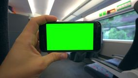Hand Holding a Phone with a Green Screen on the Train. Tbilisi, Georgia - 15 September 2017: A hand holding using a smapthone with a green screen on the train Royalty Free Stock Photos