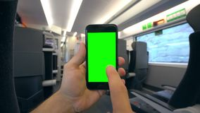 Hand Holding a Phone with a Green Screen on the Train. Tbilisi, Georgia - 15 September 2017: A hand holding using a smapthone with a green screen on the train Stock Image
