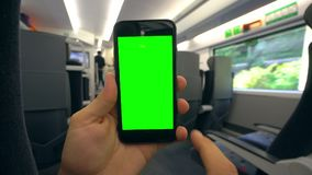 Hand Holding a Phone with a Green Screen on the Train. Tbilisi, Georgia - 15 September 2017: A hand holding using a smapthone with a green screen on the train Stock Photo