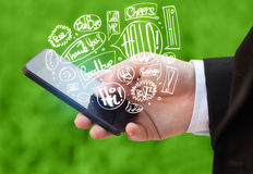 Hand holding phone with hand drawn speech bubbles Royalty Free Stock Photos