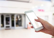 Hand holding phone in mall shopping centre. Digital composite of hand holding phone in mall shopping centre Royalty Free Stock Photo