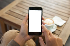 Hand holding phone mobile blank screen and finger touch. Close-up hand holding phone mobile blank screen and finger touching in coffee shop stock photography