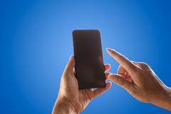 Hand holding phone mobile and touching screen isolated on blue Royalty Free Stock Photo