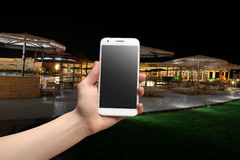 Hand holding a phone at night.  Royalty Free Stock Image