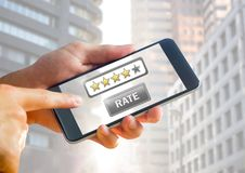 Hand holding phone with rate button and star review icons. Digital composite of Hand holding phone with rate button and star review icons royalty free stock images