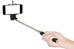 Hand holding phone selfie stick isolated with clipping path. On white Royalty Free Stock Image