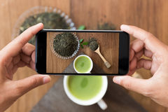 Hand holding phone shooting drink photograph Stock Photos