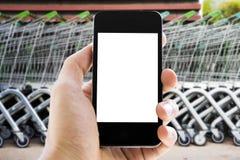 Hand holding phone on shopping cart  background Royalty Free Stock Photos