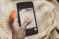 Hand holding phone and taking photo of pumpkin and leaf on warm Stock Photography