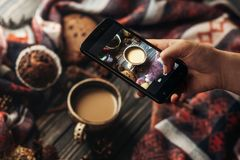 Hand holding phone taking photo of stylish winter flat lay coffe. E cookies and spices on wooden rustic background. cozy mood autumn. instagram blogging workshop Stock Photos