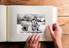 Hand holding photo album with pictures of senior couple. Studio. Hand of unrecognizable person holding a photo album looking at various black and white pictures stock photos
