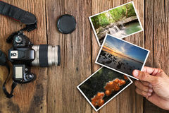 Hand holding photos with old grunge camera and photos on v Stock Photos