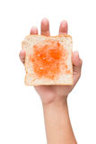 Hand holding a piece of bread with jam isolated on white Stock Image