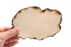 Hand holding piece of burned paper Royalty Free Stock Image