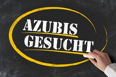 Hand holding piece of chalk against blackboard with text AZUBIS GESUCHT. German for apprentices or trainees wanted royalty free stock photography