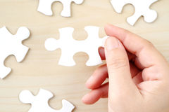 Hand holding a piece of jigsaw puzzle, background Royalty Free Stock Image