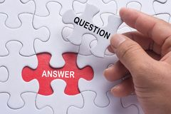 Hand holding piece of jigsaw puzzle with word question & answer. Hand holding piece of jigsaw puzzle with word question & answer Royalty Free Stock Photo