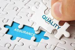 Free Hand Holding Piece Of Puzzle With Word QUALITY ASSURANCE. Stock Photo - 148859700