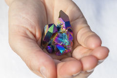 Hand holding a piece of Rainbow titanium aura Royalty Free Stock Image