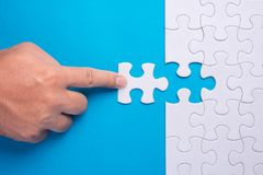 Hand holding piece of white puzzle on blue background. Business. And team work concept stock images