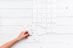 Hand holding a piece of white uncompleted puzzle Stock Photo