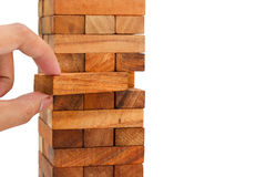 Hand holding a piece of wood block in the strategy game on white Royalty Free Stock Images