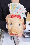 Hand holding piggy bank and Euro Royalty Free Stock Images