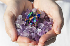 A hand holding a pile of amethyst and a rainbow titanium aura piece Royalty Free Stock Photo
