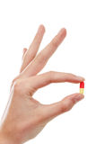 Hand holding a pill between thumb and forefinger. Isolated on white background Stock Image