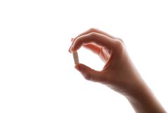 A hand holding a pill Royalty Free Stock Photography