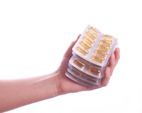 Hand holding  pills on white background Royalty Free Stock Photos