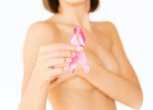 Hand holding pink breast cancer awareness ribbon. Healthcare and medicine concept - womans hand holding pink breast cancer awareness ribbon stock image