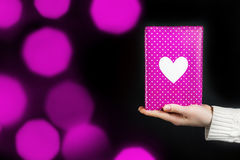 Hand holding pink gift isolated on black. Background Royalty Free Stock Images