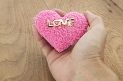 Hand holding pink heart on wood background. S stock image
