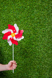 Hand holding pinwheel over grass Royalty Free Stock Photo
