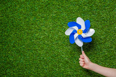 Hand holding pinwheel over grass Royalty Free Stock Images
