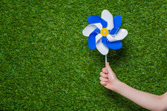 Hand holding pinwheel over green grass Royalty Free Stock Photos
