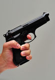 Hand holding a pistol. Isolated on grey background Royalty Free Stock Photo